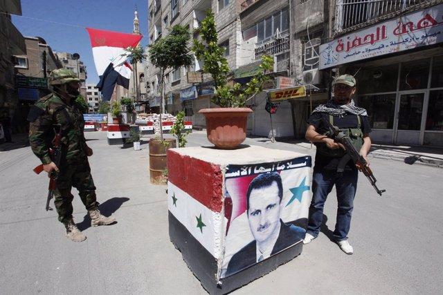 Soldados y milicianos leales al gobierno sirio en Damasco