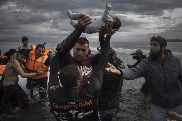 Un voluntario sostiene a un bebé mientras otros ayudan a desembarcar a un grupo