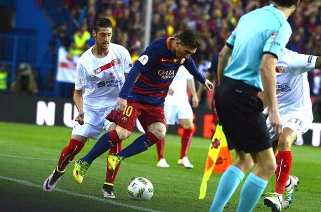 Sergio Escudero, del Sevilla, ante el barcelonista Lionel Messi