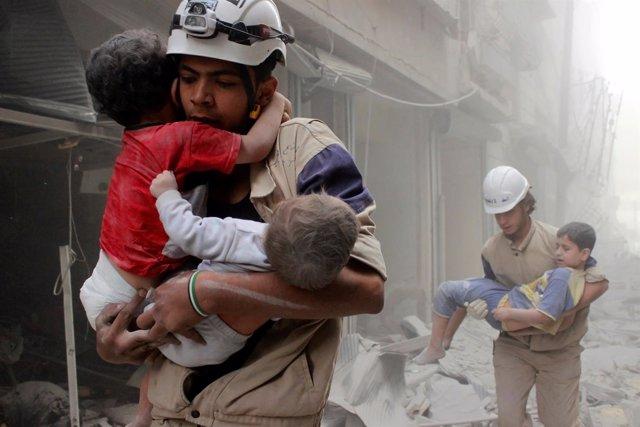 Cascos blancos con niños rescatados tras bombardeo en Alepo