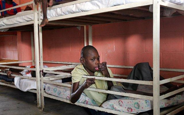 Un niño haitiano sentado sobre su cama en un orfanato en Puerto Príncipe.