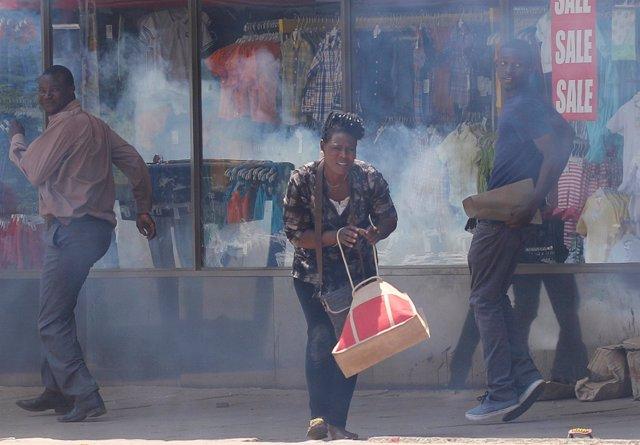 Varios ciudadanos huyen del gas lacrimógeno lanzado por la Policía en Harare.