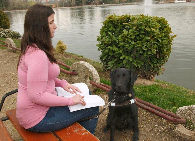 Una joven invidente lee en braille junto a su perro guía