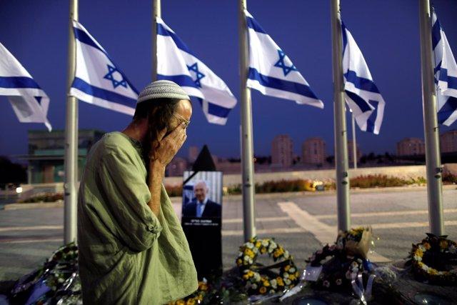 Un hombre llora junto al retrato de Shimon Peres en Jerusalén.