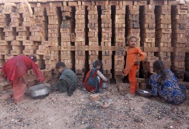 Niños afganos trabajando en una fábrica de ladrillos