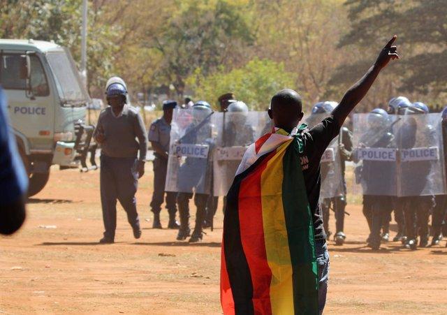 Manifestante opositor delante de la Policía en Harare
