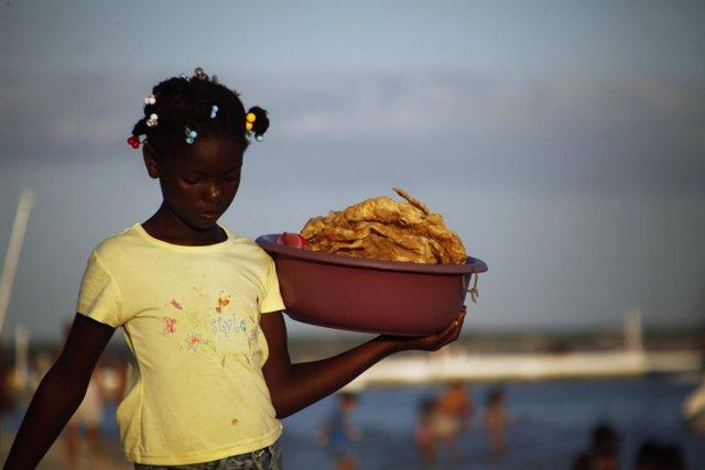 Niña trabaja en playa de República Dominicana