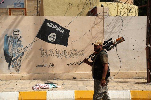 Un militar iraquí junto a la bandera de Estado Islámico en Shirqat