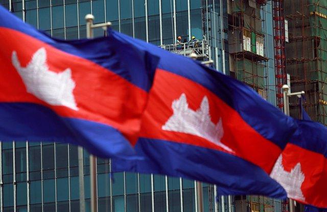 Banderas nacionales de Camboya frente a un edificio en construcción