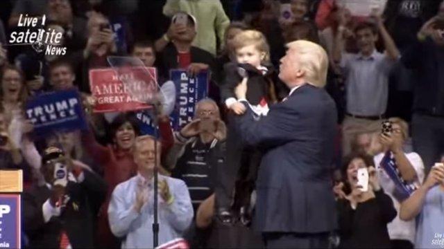 Trump sujeta a un niño disfrazado como él durante un mitin