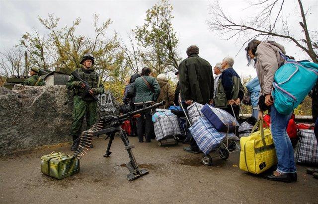 Personas esperando para cruzar en un puesto de control en Lugansk