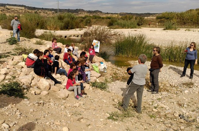 Un grupo de niños atiende las indicaciones de un monitor, cerca del río.
