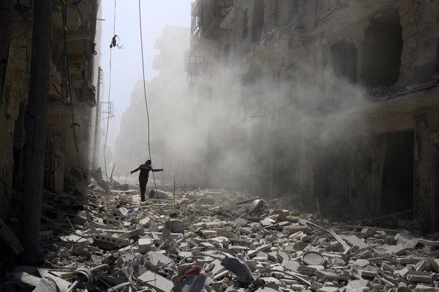 Una persona camina entre escombros en una zona rebelde de Alepo