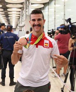 Carlos Coloma muestra su medalla a su llegada a España desde Río de Janeiro
