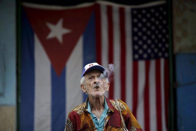 Un cubano fuma un puro ante las banderas de EEUU y Cuba