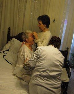 Una usuaria del SAD es atendida por su hija y una cuidadora