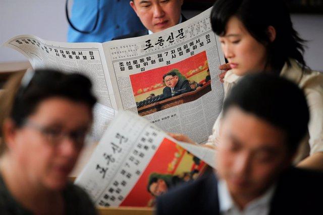 Norcoreanos con periódicos propagandísticos en los que aparece Kim Jong Un