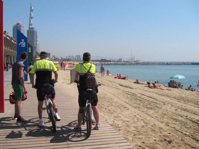 Dos agentes de la Guardia Urbana en la playa del Somorrostro de Barcelona