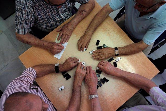 Pensionistas juegan al dominó en un centro de mayores
