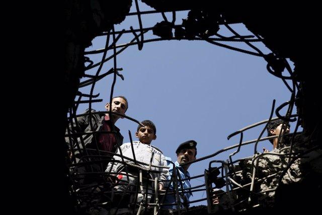 Yemeníes miran a través de un agujero dejado por una bomba en Saná