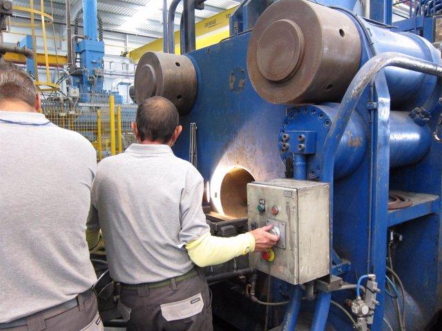 Dos operarios manipulando una máquina en una fábrica.