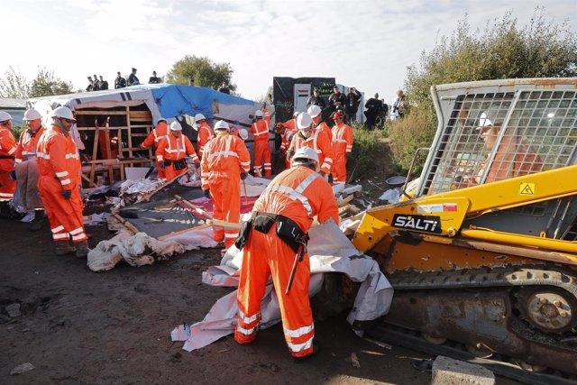 Un grupo de operarios retira tiendas en el campamento de Calais