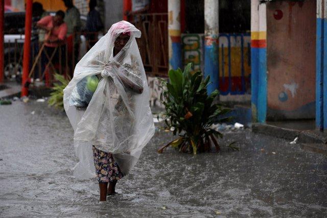 Una mujer caminapor una calle anegada en Haití