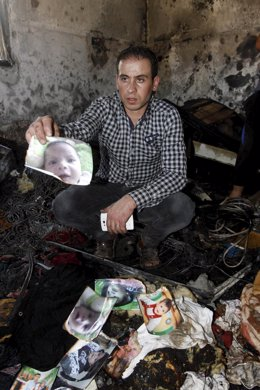Un pariente del bebé palestino muerto muestra un retrato del bebé