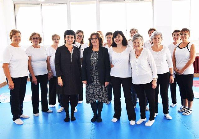 La consejera María Victoria Broto, junto a alumnos de Yoga, este jueves.