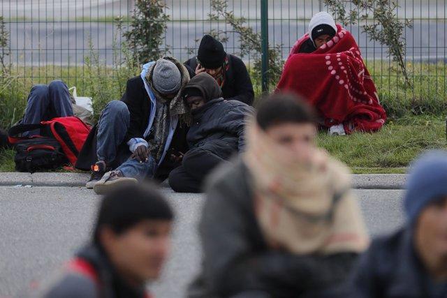 Un grupo de refugiados se prepara para pasar la noche fuera de la 'jungla'.