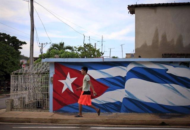 Un hombre camina junto a la bandera de Cuba en Holguín