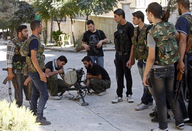 Rebeldes sirios revisan sus armas en la ciudad de Alepo
