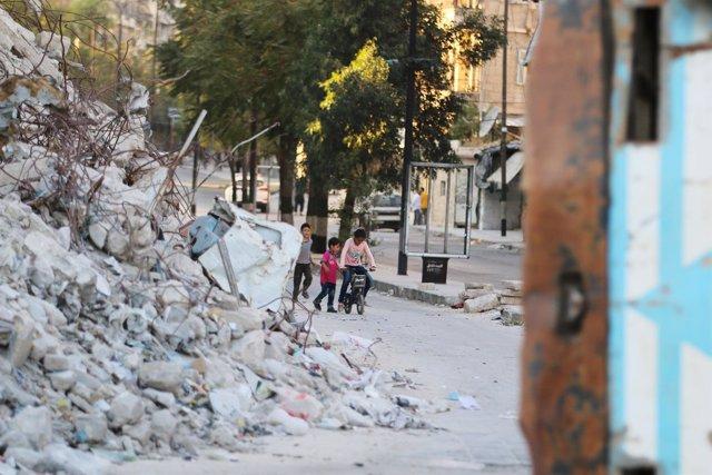 Unos niños juegan junto a un edificio destruido en Alepo