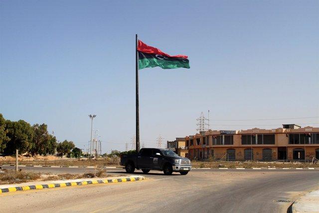 Una bandera libia ondea a la entrada de Sirte