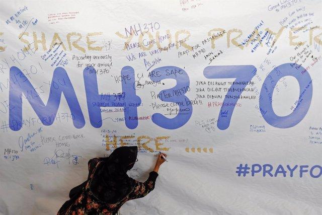Una mujer escribe un mensaje de apoyo y esperanza por el vuelo MH370
