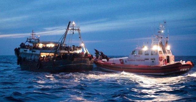 Patrullera de la Guardia Costera italiana junto a un barco con inmigrantes