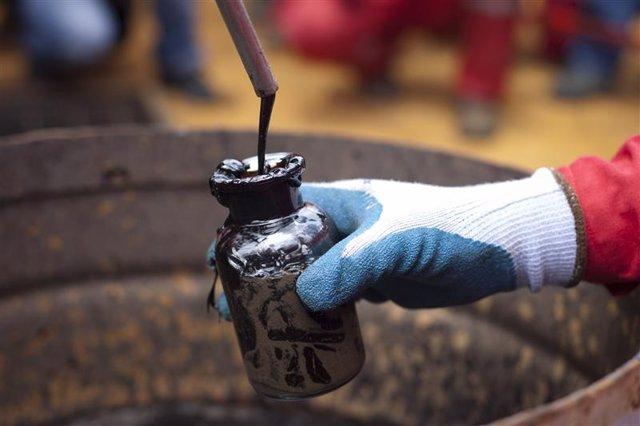 Un trabajador recolecta una muestra de crudo en un pozo de PDVSA en Morichal