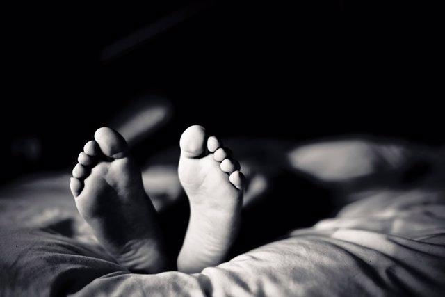 Pies, cama, piernas inquietas