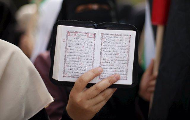 Una mujer muestra un ejemplar del Corán