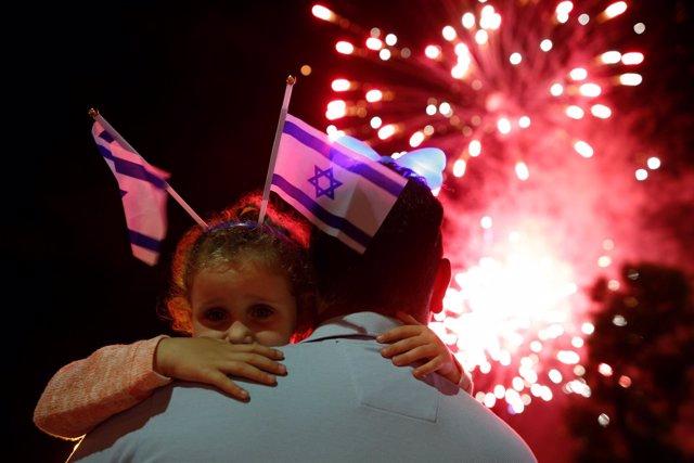 Una niña durante una celebración con banderas israelíes
