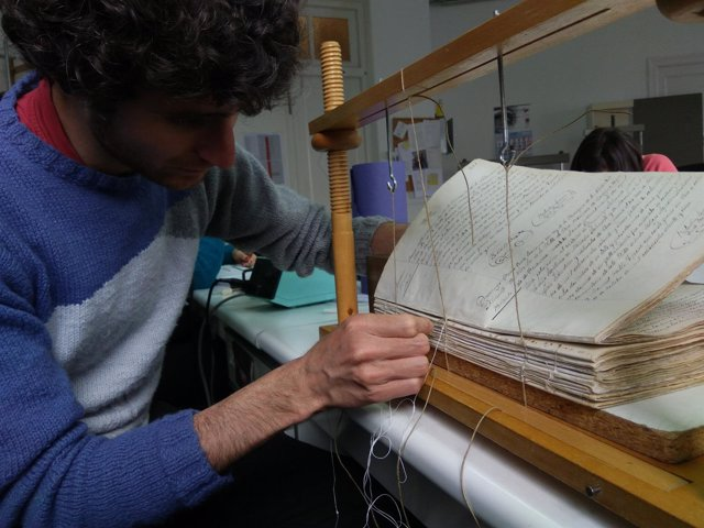 Un alumno de la escuela taller de la DPZ restaurando los libros sacramentales