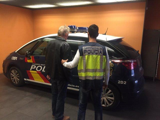 Un agente traslada al detenido en Pego