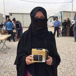 Una mujer iraquí sonríe mostrando su radio cerca de Mosul, Irak
