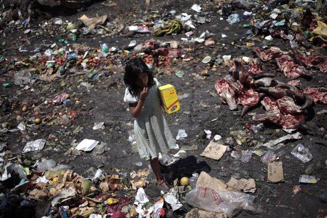 Niña jugando entre los escombros en Guatemala