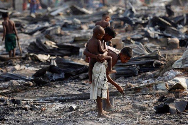 Niños rohingya buscan entre restos de casas incendiadas en Rajine, Birmania