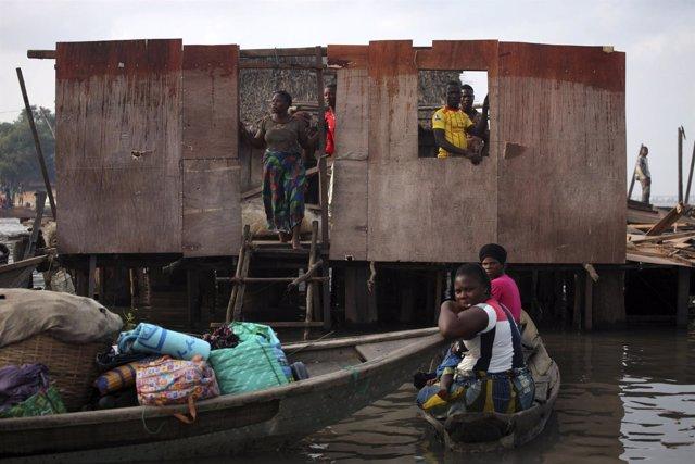 Residentes de la comuniad de Makoko en Laos observan la demolición de viviendas.