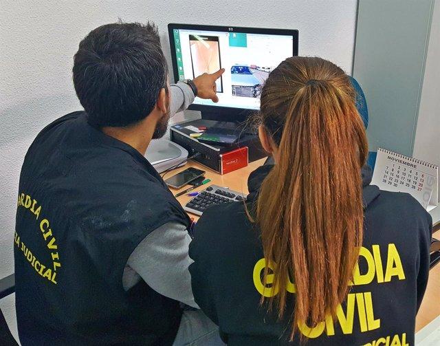 Dos guardias civiles frente a la pantalla de un ordenador