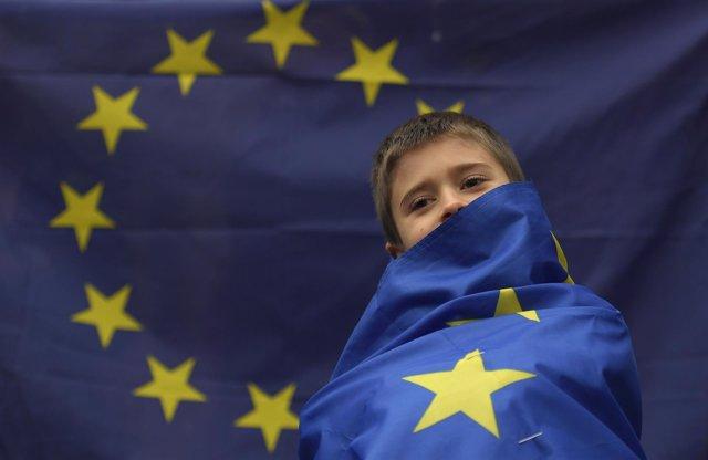 Niño envuelto en una bandera de la UE