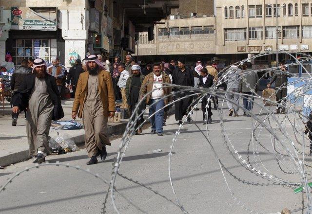 Varios residentes de Mosul caminan junto a un alambre de espino.