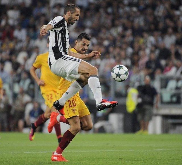 Chiellini y Vitolo pugnan por un balón en la primera vuelta del Juventus-Sevilla